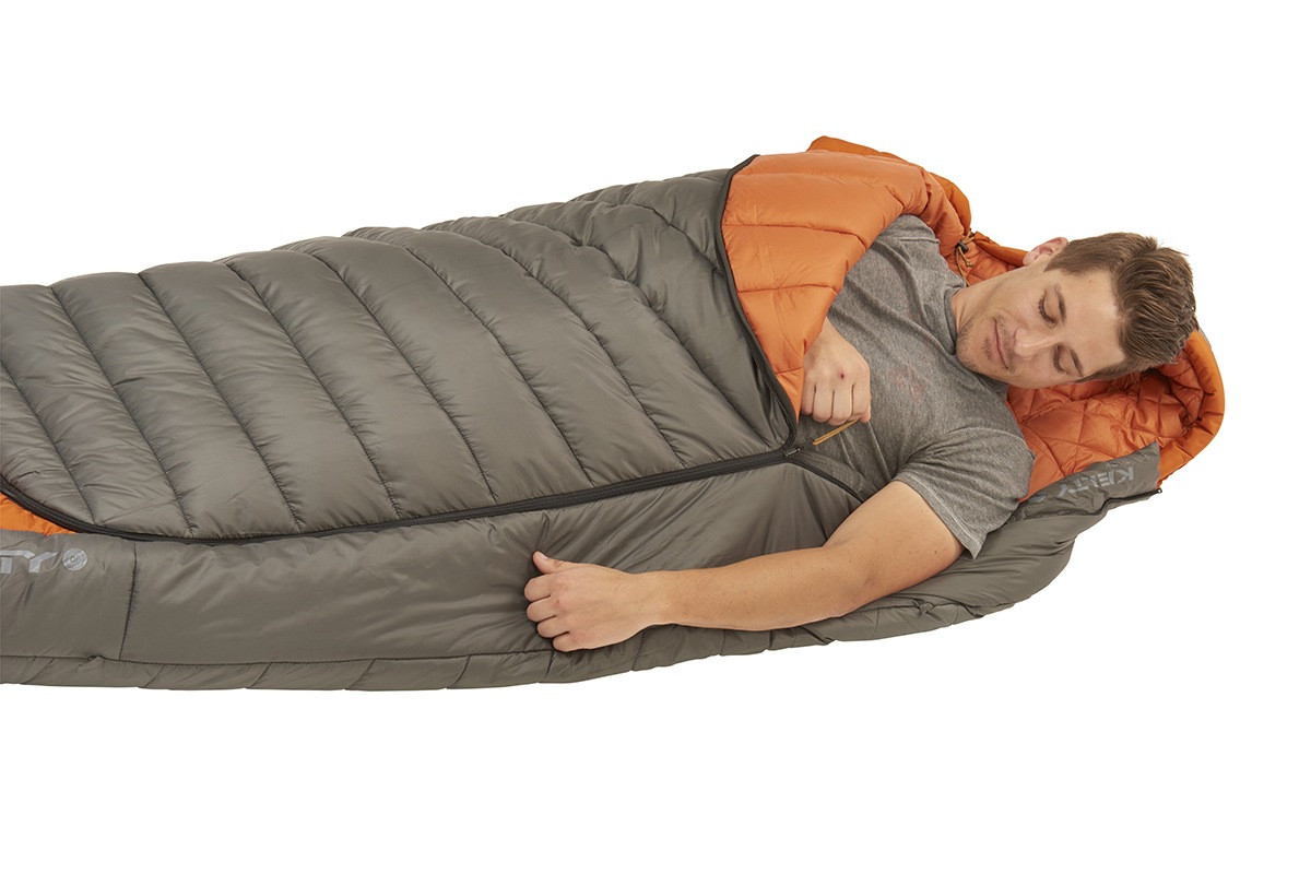 Man sleeping in Kelty Tuck 0 Degree Sleeping Bag, with arm extended outside of bag