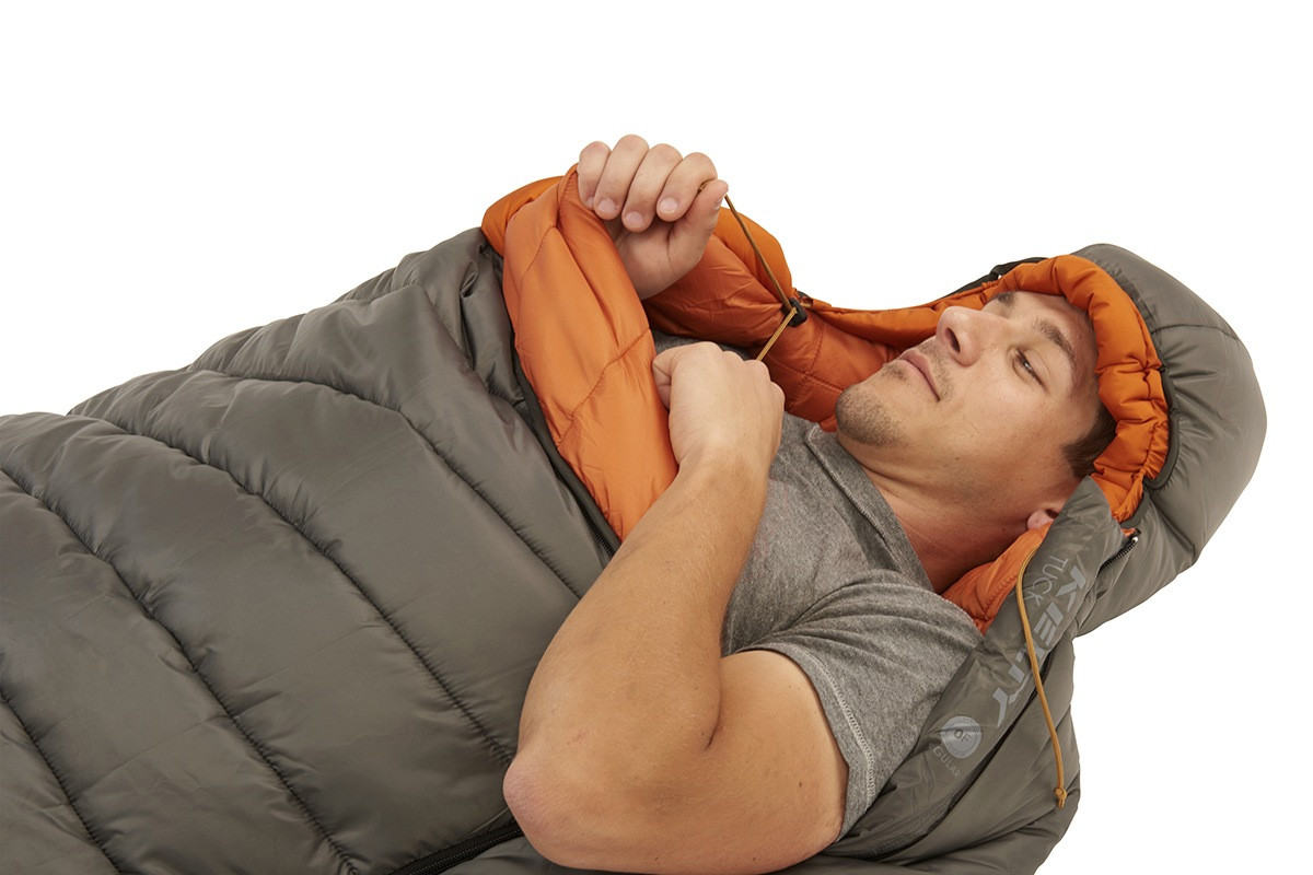 Man inside of Kelty Tuck 0 Degree Sleeping Bag, pulling the drawcord of the bag's hood