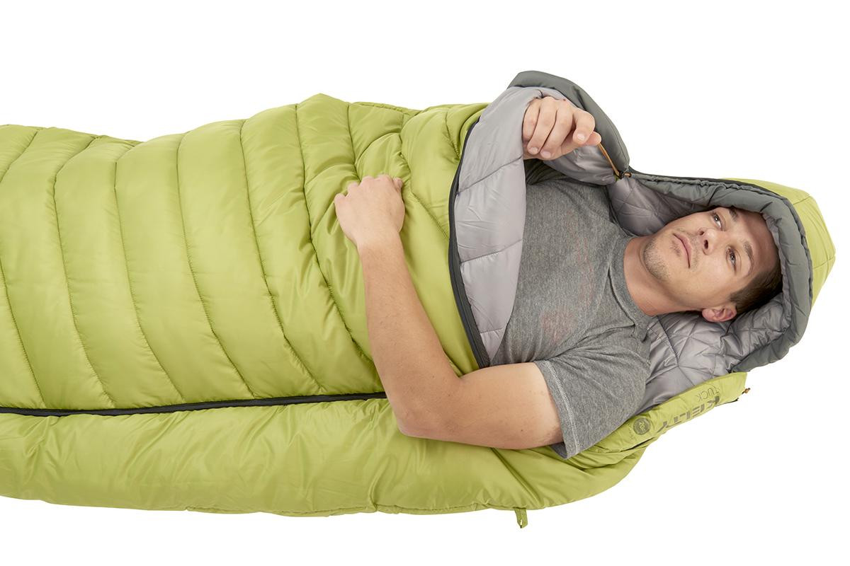 Man in Kelty Tuck 20 Degree Sleeping Bag, pulling the drawcord of the bag's hood