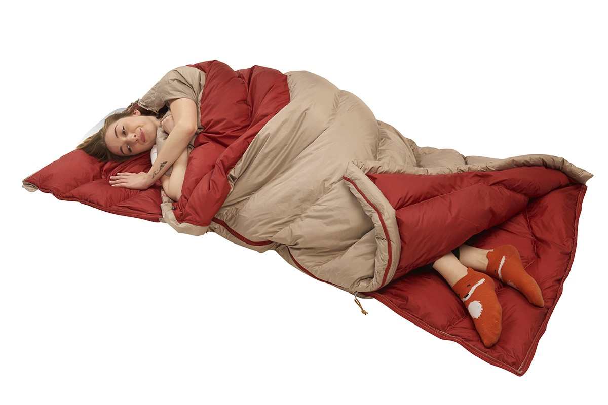 Woman in Kelty Women's Galactic 30 Dridown sleeping bag, sleeping on her side, with bottom of bag unzipped, venting her feet