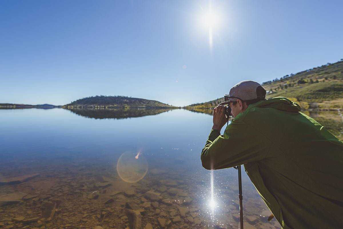 Photographer using a Kelty Snapshot trekking pole to keep his camera steady while shooting a lake