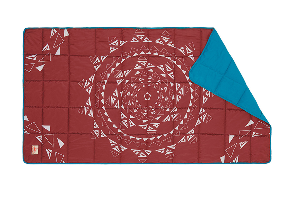 Limited Edition Bestie Blanket, top view, showing geometric pattern of gray triangles arranged in a circle on a dark red background
