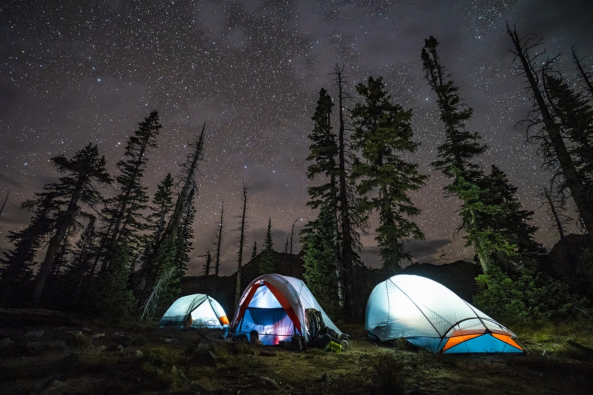 Kelty All Inn 3 Person Tent, blue colorway, at nighttime in the forest