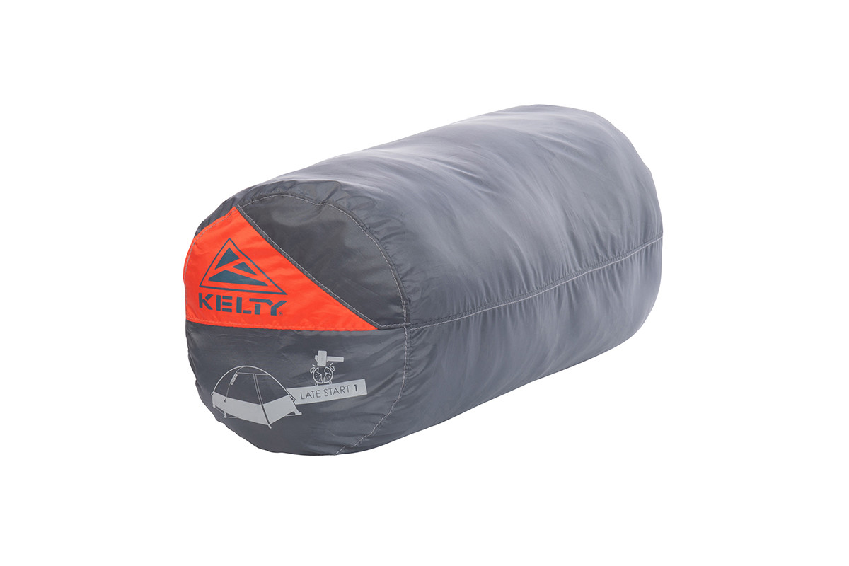 Kelty Late Start 1 person tent packed inside gray cylinder-shaped storage bag