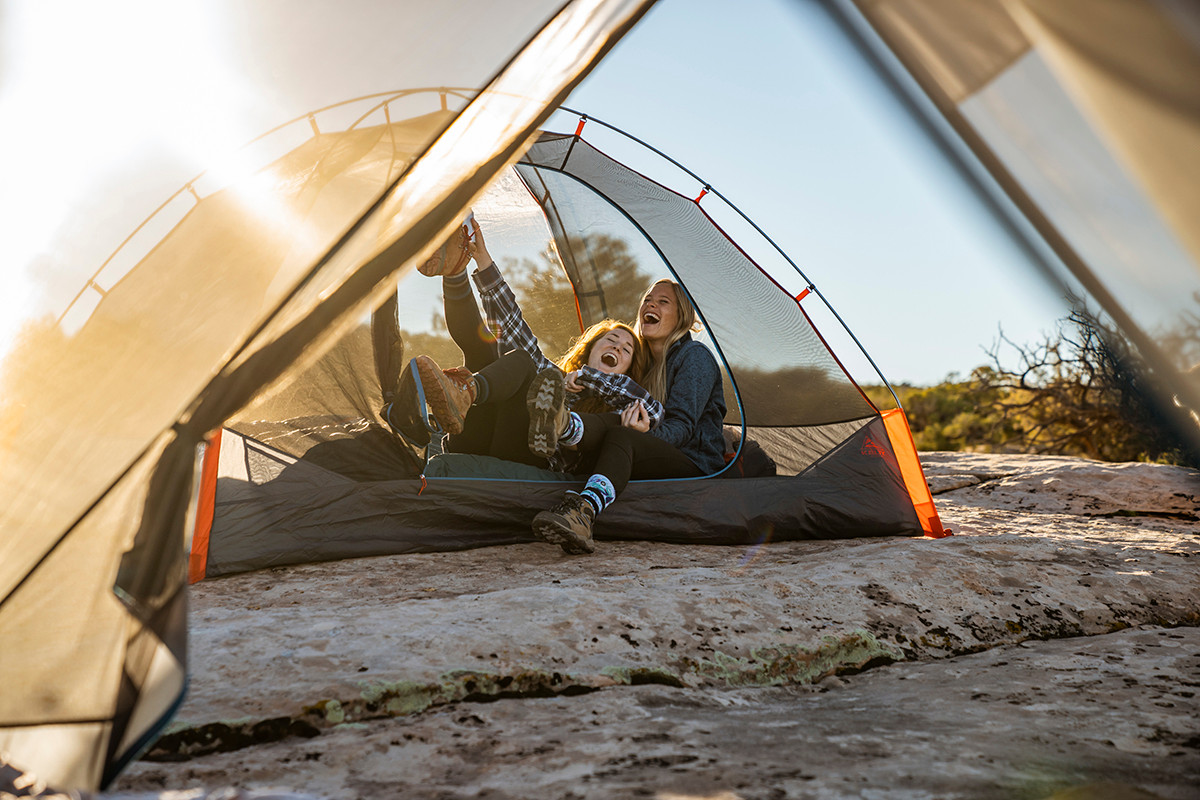Two women inside Kelty Late Start 2 person tent, laughing