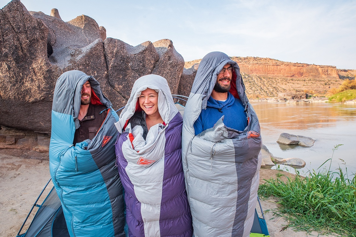 Group of 3 friends wearing Kelty Cosmic 40 sleeping bags, next to lake
