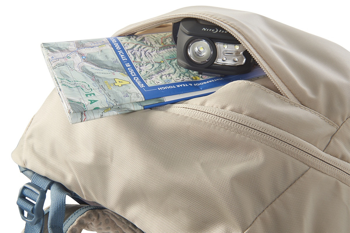 Close up of Kelty Women's Zyp 28 backpack, showing map and headlamp stored in lid
