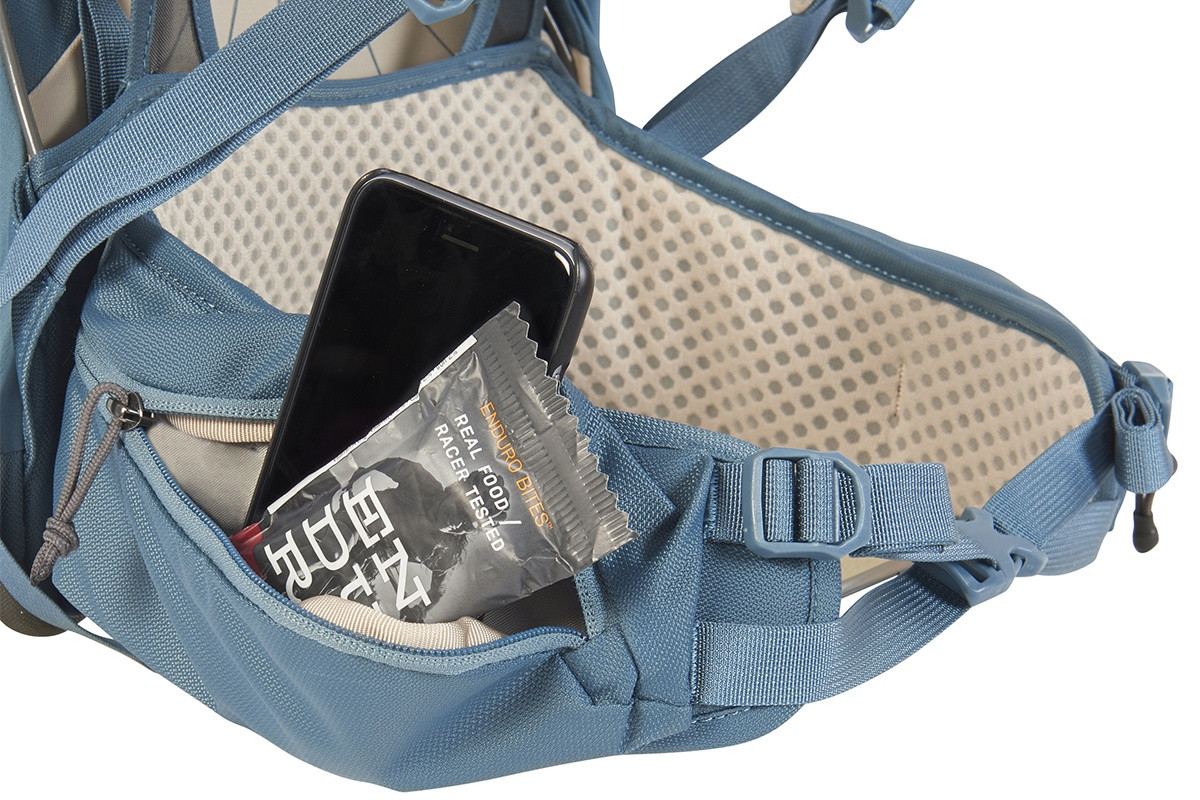Close up of Kelty Women's Zyp 28 backpack, showing snacks and phone in waist belt pocket