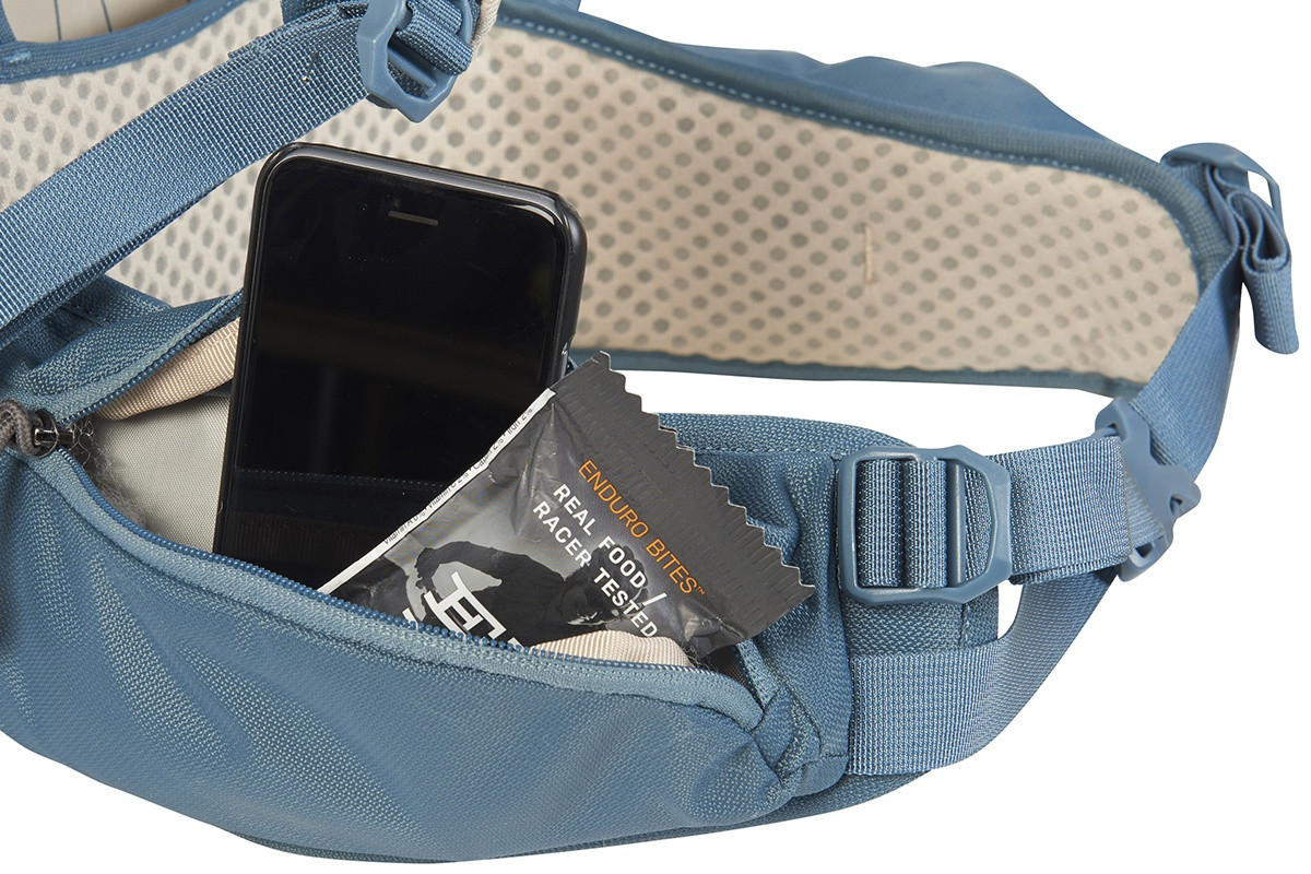 Close up of Kelty Women's Zyp 38, showing snacks and phone in waist belt pocket