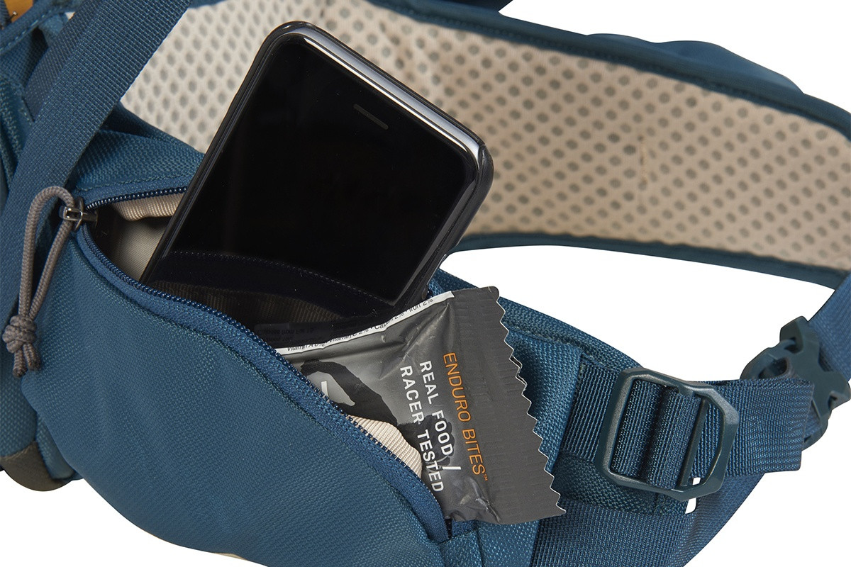 Close up of Kelty Zyp 48 backpack, showing phone and snacks stored in waist belt pocket