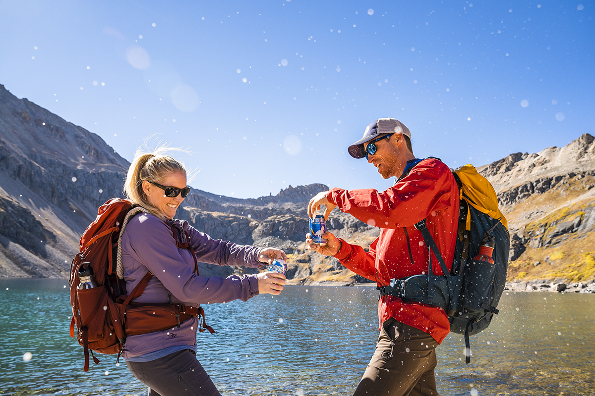 Couple with Kelty Zyp 48 backpacks, opening cans of beer in front of a lake