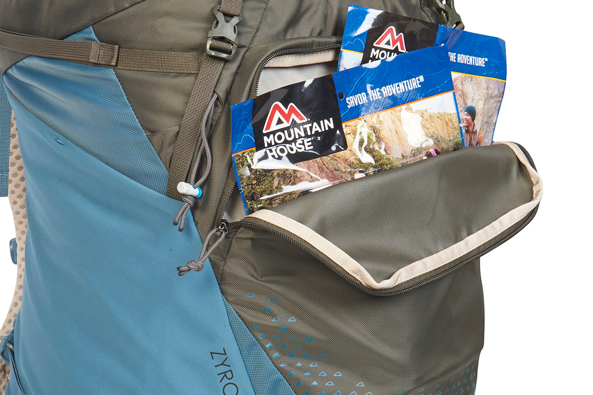 Close up of Kelty Women's Zyro 64 backpack, with front compartment unzipped to show multiple bags of dehydrated backpacking meals inside