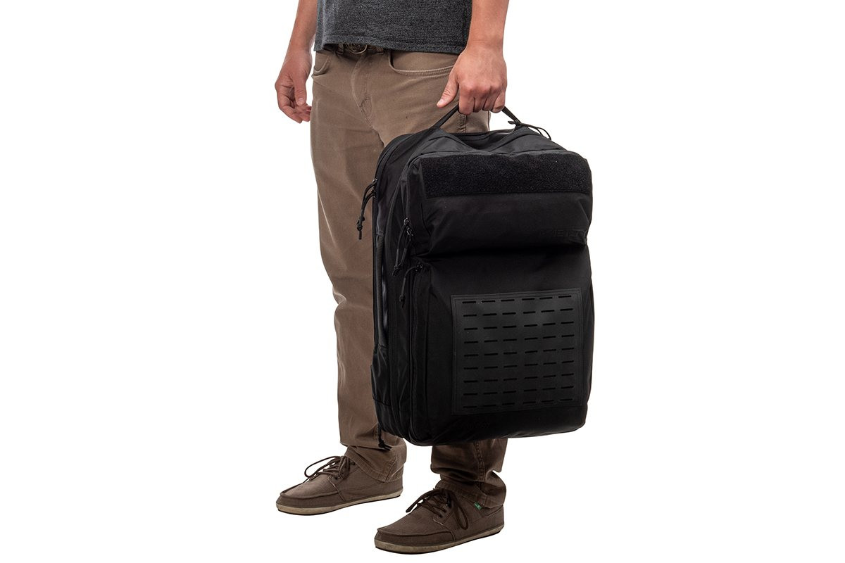 Man holding Kelty Nomad travel pack with top handle