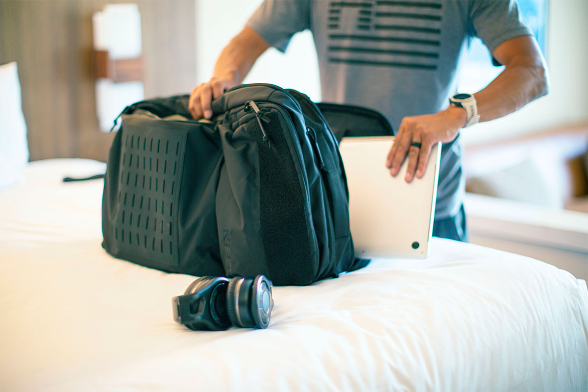 Man putting laptop into the laptop sleeve inside the Kelty Nomad travel pack
