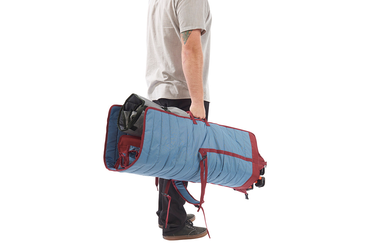 Man carrying Kelty Discovery Low-Love 2-person chair, blue/red, in its storage tote