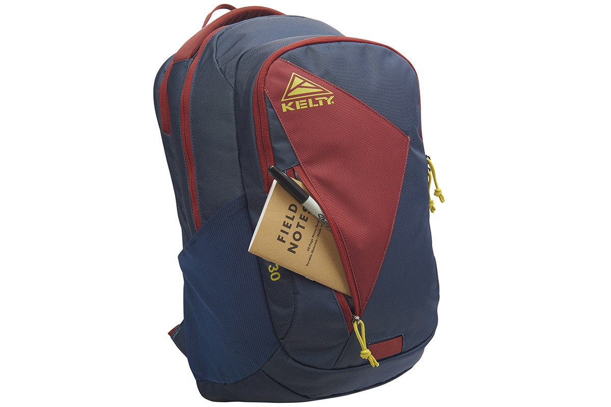 Kelty Slate 30 Daypack, Midnight Navy/Red Ochre, with notebook and pen partially extending from front external pocket