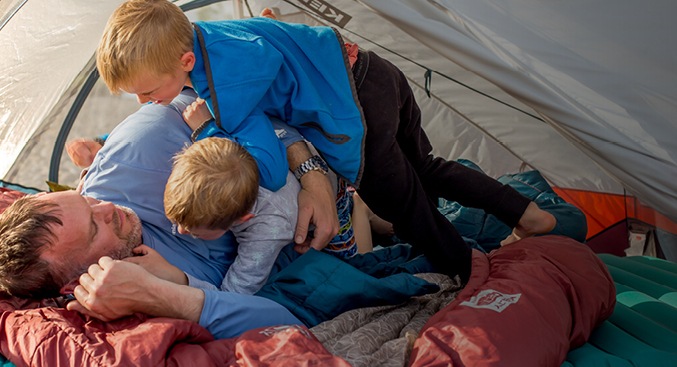 Three friends standing in front of tent while wearing sleeping bags