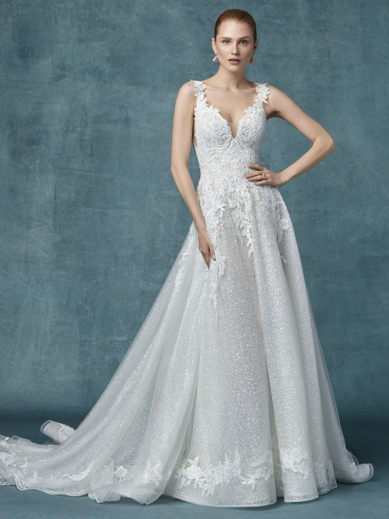 6447f3e02764e Maggie Sottero Carmella. Romantic lace motifs drift over the bodice and  hemline of this unique