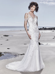 Sottero and Midgley Georgina.  Channeling Old Hollywood glamour and sophistication, this vintage-inspired sheath wedding dress features swirls of beading and Swarovski crystals over tulle. Intricate beadwork on tulle complete the cold-shoulder sleeves, V-neckline, and dazzling illusion scoop back. Detachable beaded back feature adds a special touch to this glamourous gown. Finished with crystal buttons over zipper closure. Available in: Ivory, Ivory over Light Gold, Ivory over Soft Blush.