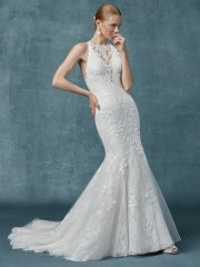 Maggie Sottero Liberty.  This lace gown features lace motifs atop allover lace in a fit-and-flare silhouette. Complete with illusion halter over plunging V-neckline and illusion halter back. Finished with covered buttons over zipper closure. Available in: All Ivory, Ivory over Soft Blush (pictured).