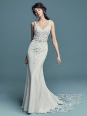 Maggie Sottero Alaina.  Embroidered lace motifs accented in pearls and Swarovski crystals cascade over the sheer bodice of this romantic Aldora Crepe wedding dress, completing the straps, V-neckline, and illusion scoop back. Sheath skirt features an illusion cutout train accented in lace motifs and an attached beaded belt with Swarovski crystals. Finished with pearl buttons and zipper closure. Available in: Ivory, Ivory over Nude, shown.