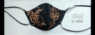 Floral cloth mask - black with henna-style bleached-out design in orange.