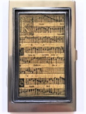 "Bronze colored durable & unique metal case Size:  2.25"" x 3.75"" x .31"" Vintage music notes artwork encased in multi layer hand poured resin for durability Handmade in Los Angeles by KBD Design"