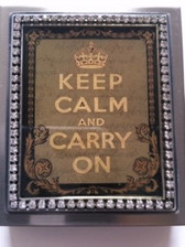 "Bronze colored durable & unique metal pill box case Size:  2.38"" x 2.81"" x .31"" Keep Calm and Carry On artwork with sparkle effect encased in multi layer hand poured resin for durability Clear Swarovski crystals border framing artwork   Handmade in Los Angeles by KBD Design"