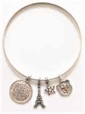 From the Old Silver collection Sterling silver over a copper base metal Smooth thin width bangle is .12 Charms:  Decorative Paris coin; Eiffel tower with clear Swarovski crystals; star with clear Swarovski crystals; fleur de lis emblem;  Charms make a delightful noise when in motion! By La Vie Parisienne