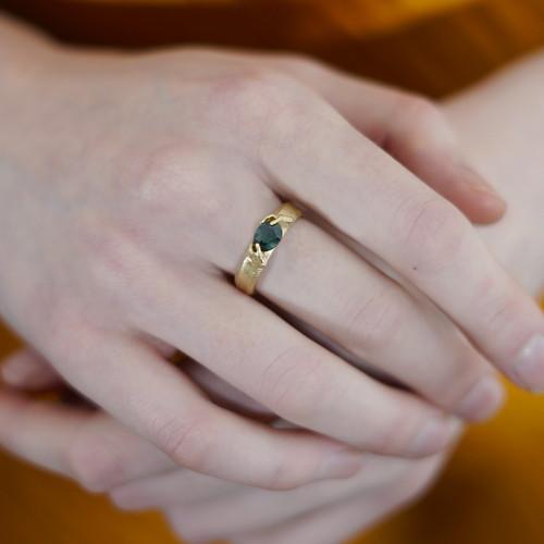 Fraser_Hamilton_handmade_jewellery_ring_14K_yellow_gold_green_sapphire_stone_tiny_hands_holding_sculptural_jewellery