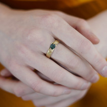 Fraser_Hamilton_handmade_jewellery_ring_14K_yellow_gold_green_sapphire_stone_tiny_hands_holding_sculptural_jewellery