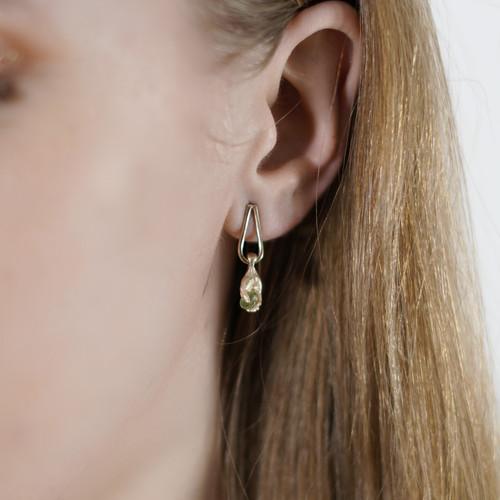 Fraser_Hamilton_handmade_jewellery_earrings_14K_yellow_gold_hands_dropping_dangling_green_sapphires_holding_sculptural_jewellery