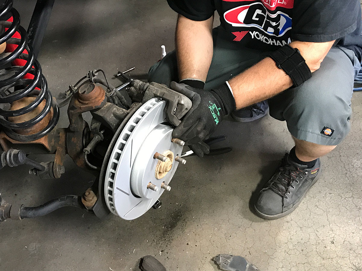 R1 Performance rotors and pads being installed on the front of the GenRight Grey Wolf JK