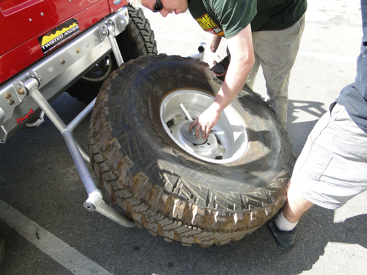 Tighten the T-handle to press the tire into the carrier cage.