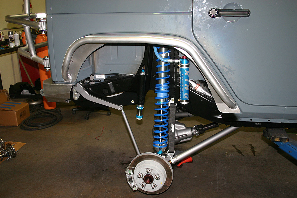 It mounts above the frame in the rear and ties into the Elite shock mount