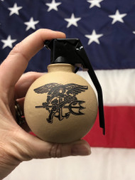 - Made in the USA - Steel Casting with a Sheet Metal Spoon; uniquely different not perfectly symmetrical - Noticeable imperfections, dents, divots and elevated ridges - Desert Sand Color with Trident on one side and Navy SEAL Museum Shooter Logo on the other  - Comes in a splendid wooden gift box  - Do NOT take this into the airport  This frag grenade bottle opener will open all of your bottles and have your friends asking if they can try it and then where they can buy  Made by Bottle Breacher A Veteran Owned and Operated businesses started by Former Navy SEAL, Eli Crane, and his wife Jen who brought it to Shark Tank