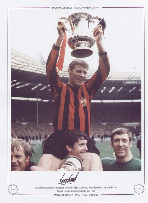 Manchester City captain Tony Book, surrounded by his teammates, holds aloft the FA Cup after his side defeated Leicester City in the 1969 FA Cup Final.