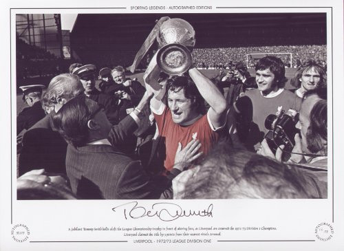 A jubilant Tommy Smith holds aloft the League Championship trophy in front of adoring fans, as Liverpool are crowned the 1972/73 Division 1 Champions. Liverpool claimed the title by 3 points from their nearest rivals Arsenal. Great addition to any collection.