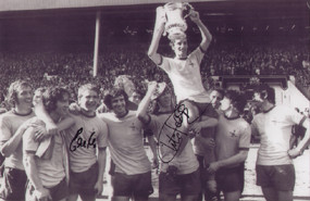 """Frank McLintock is chaired by team-mates after the 1971 FA Cup Final. The photograph is 12"""" x 8"""" (305mm x 205mm) and has been signed by Charlie George & Eddie Kelly."""