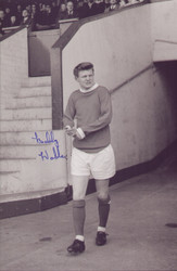 "Signed by: Bobby Noble     12"" x 8"" (305mm x 205mm) Photograph     Certificate of Authenticity Provided  Born in Stockport, Noble signed for Manchester United as a trainee in 1961 and turned professional the following year. He made his Football League debut on 9 April 1966 in a 2–1 home defeat to Leicester City and became a regular in the side that won the league title in 1967. he was seriously injured in a car crash just before United sealed the title. He recovered from the injuries which almost claimed his life, but his attempts to recover full fitness proved unsuccessful and he retired from playing three years later."