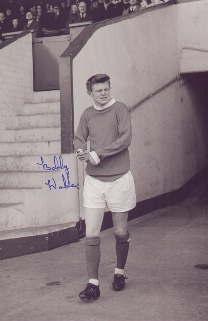 """Signed by: Bobby Noble     12"""" x 8"""" (305mm x 205mm) Photograph     Certificate of Authenticity Provided  Born in Stockport, Noble signed for Manchester United as a trainee in 1961 and turned professional the following year. He made his Football League debut on 9 April 1966 in a 2–1 home defeat to Leicester City and became a regular in the side that won the league title in 1967. he was seriously injured in a car crash just before United sealed the title. He recovered from the injuries which almost claimed his life, but his attempts to recover full fitness proved unsuccessful and he retired from playing three years later."""