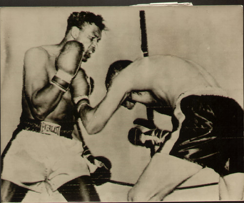 On offer is an original radio/wire photograph showing Sugar Ray Robinson in action against Carl Bodo Olson, Robinson retained his title after knocking Olson out in the fourth round of their World Middleweight title fight in Los Angeles 18 May 1956.