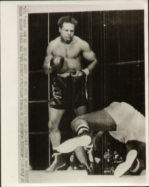 original radio/wire photograph showing Archie Moore standing over Rocky Marciano after knocking him down in the second round of their World Heavyweight title fight held at the Yankees Stadium, New York in front of over 61000. Marciano retained his title after finally knocking Moore out in the ninth round.