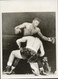 "On offer is an original radio/wire photograph showing World Heavyweight Champion Floyd Patterson in action as Tom McNeeley drops to one knee in the first round of their title fight held on December 4, 1961 at Maple Leaf Gardens in Toronto. Patterson retained his title after finally knocking McNeeley out in the fourth round.  Superb 8"" x 6"" (205mm x 150mm approx) picture and great addition to any boxing collection."
