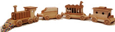 A smaller version of my signature interactive eight car wooden train, the Circus Train includes an engine with an engineer, a tender with blocks, a circus car with a giraffe and elephant, and a caboose with two passengers and a removable roof. Each car is designed to maximize a child's interactive and imaginative play skills, and the train can be pulled by a rope. The Circus Train is over 48 inches long by 6 inches high by 5 inches wide. The cars are hand crafted from maple, cherry, walnut, oak, and birch, and as with all my toys, finished with fine sanding.