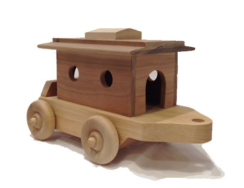 """What train would be complete without a caboose to carry the passengers? Ours arrives with two little people looking out the windows. The roof is easily removed so the people can get in and out. The caboose is 10"""" long x 4"""" wide."""