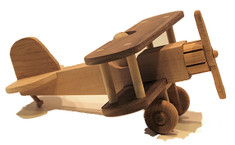 "This nostalgic biplane features a working propeller and pilot, and captures the fancy of aviators past, present and future. Although it rests on landing wheels, most children fly it with outstretched arms while saying ""vroom, vroom."" Crafted out of oak, walnut, maple, and cherry. The biplane is 10"" long x 11"" wide x 5"" high."