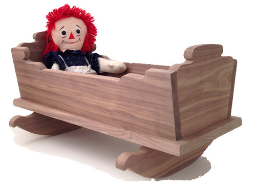 "Large enough to hold a favorite baby doll, stuffed animal, or a family of little ones, this detailed and durable cradle from yesterday will be enjoyed today and then saved for tomorrow. Crafted out of solid walnut, the doll cradle is 21"" long x 14"" wide x 11"" high. Pictured with a Raggedy Ann doll for display purpose only."