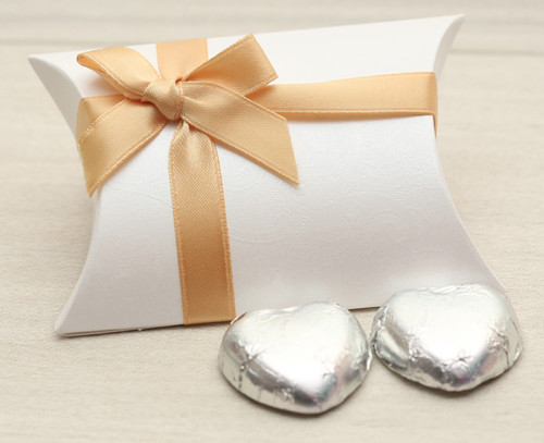 Table Gift in the shape of a Pillow Box  containing two solid milk chocolate hearts and ribboned with a gold satin ribbon.