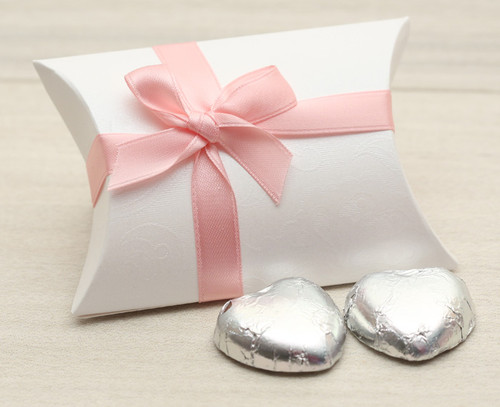 Table Gift in the shape of a Pillow Box  containing two solid milk chocolate hearts and ribboned with a Pink satin ribbon.